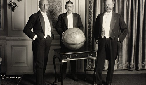 black and white of shackleton amundsen perry in formal dinner jackets around large globe on display table