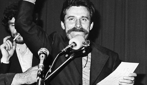 lech walesa black and white standing speaking microphone fist in air holding notes