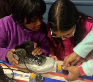 Shoba y Rosana ayudan a Lisha a colocar la bota en la fijación.