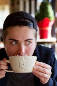 cameron drinking latte at pomegranate cafe