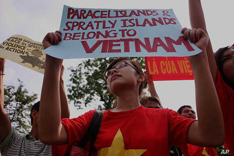 Protesters hold up Vietnamese flags and anti-China banners in front of the Chinese embassy during a protest against the alleged invasion of Vietnamese territory by Chinese ships in disputed waters in Hanoi, June 12, 2011