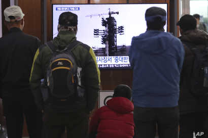 People watch a TV screen showing a file image of the North Korean long-range rocket at a launch pad during a news program at…