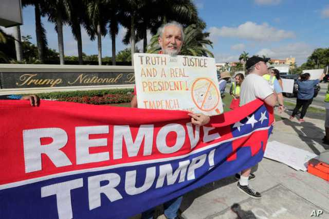 Ray Bonachea holds a sign in favor of the impeachment of President Donald Trump, outside of the Trump National Doral Miami golf…