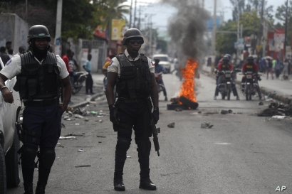 Police stand near a barricade built by protesters in Port-au-Prince, Haiti, Sept. 30, 2019.