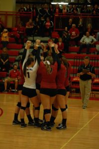 The women's volleyball team calls a huddle.
