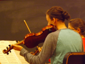 Sam Burns practices the violin during rehearsal. Photo courtesy of H.Carnahan/Setonian