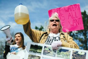 Flint resident Gladyes Williamson holds up a jug of discolored water from Flint as she protests the water crisis in April 2015. Flint residents protested for numerous reasons, including cleaner water and the resignation of Gov. Snyder. Photo courtesy of rollingstone.com