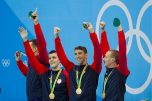 Team USA swimmers Nathan Adrian, Ryan Held, Michael Phelps and Caeleb Dressel celebrate after winning gold in the 4x100-meter freestyle relay. Photo courtesy of Wikimedia Commons.