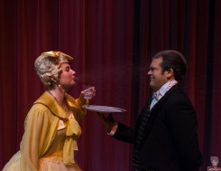 Mrs. Tottendale (Nicole Castelli) spits out her drink at Underling (Adam Sarp).