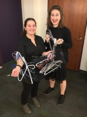 Jordyn Turner and Julie Lang smile with all their hangers from the cast's costumes.