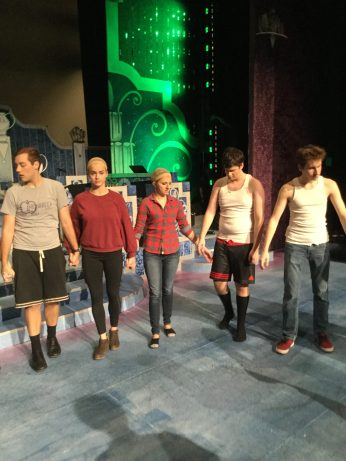 Cast members reach out to grab each other's hands as they warm up before the show.