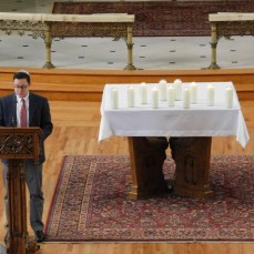 David Stanger, associate professor of art at Seton Hill University, reads the names of the 11 people who died in the shooting at the Tree of Life synagogue in Squirrel Hill during the memorial service in St. Joseph Chapel on Oct. 30. Photo by H.Carnahan/Setonian.