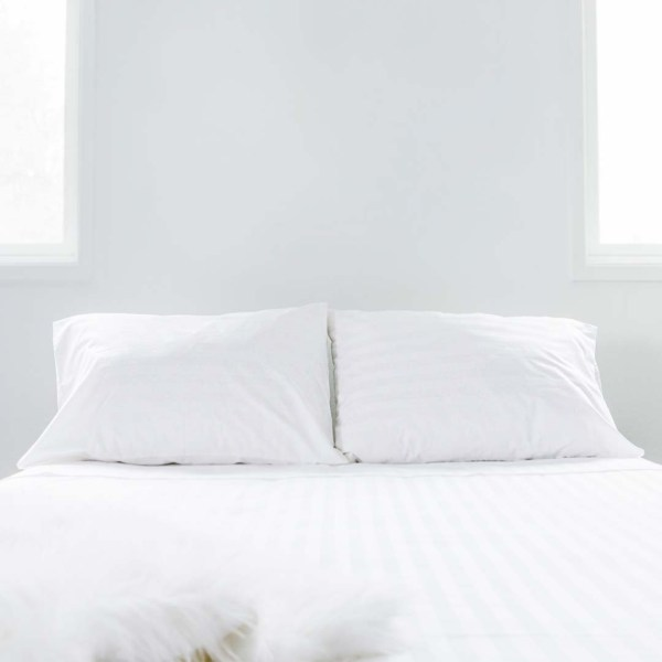 fitted sheet, flat sheet, and pillows with pillowcases on a neatly made bed