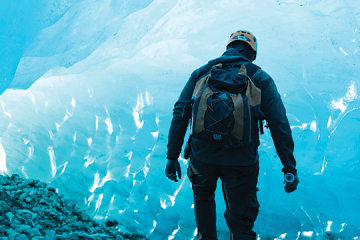 man hiking on a glacier