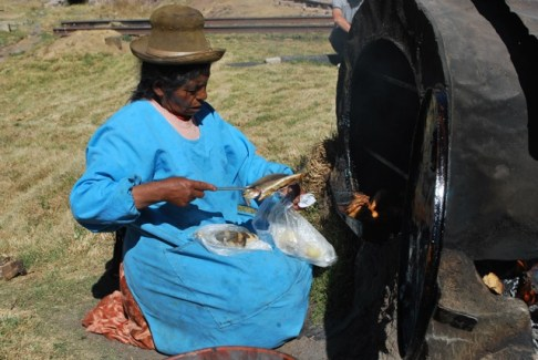 Buying baked trout for lunch, Peru.