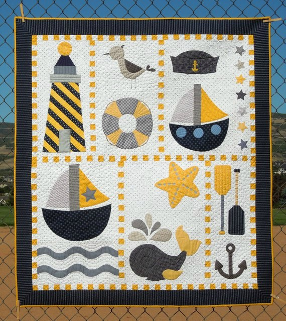 How beautiful would this nautical quilt look in a nursery or young boys bedroom? You can download the pattern and tutorial for the Ahoy Quilt Pattern below. This Nautical Quilt is absolutely full of fun and cute nautical items like a lighthouse, sailor's cap, ship's, a whale spouting water, a starfish, some oars and an anchor.