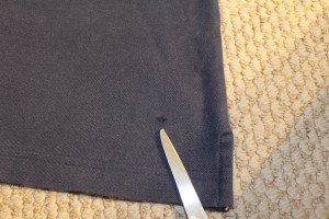 Navy blue polo with a hole near the hem.
