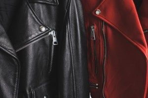 Red and black leather jackets with metallic zipper and buttons. Man and woman concept. Detailed closeup view.