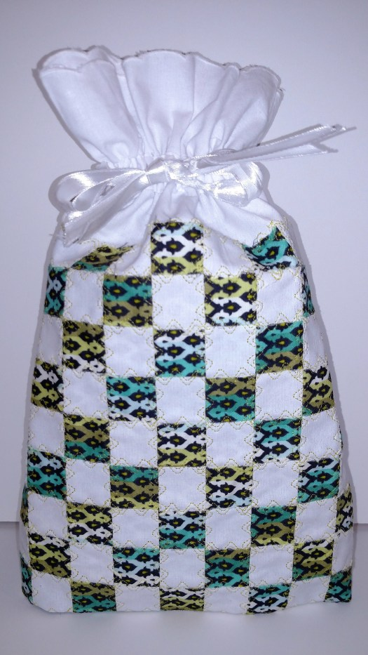 Ready made white cotton shoe bag transformed by weaving a colored fabric into the white fabric and then using decorative stitdhing to secure.