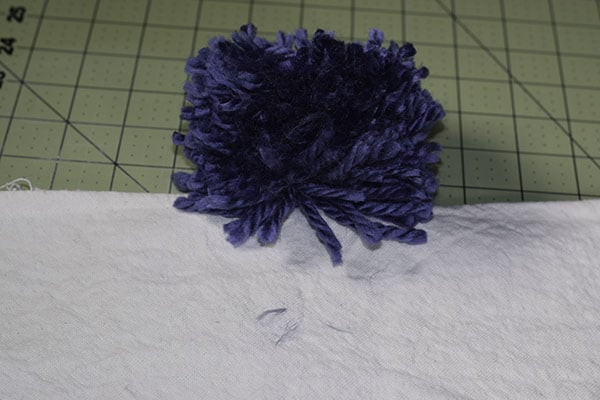 Make a drop cloth pom pom throw