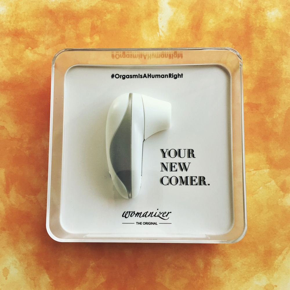 "photo of white and silver womanizer starlet inside clear square box - slogan ""your new comer"" in black"