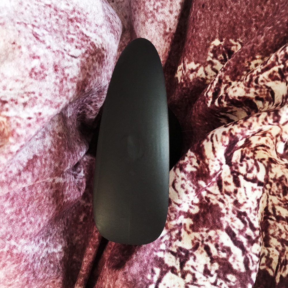 Photo of black silicone plug's oblong shaped base on pink speckled background