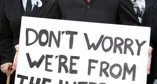 """Protest by Anonymous, people wearing Guy Fawkes masks and holding a poster saying """"Don't worry, we're from the internet."""""""