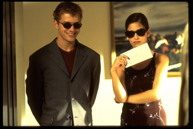 Philippe and Gellar dresses in black with dark glasses, holding a letter
