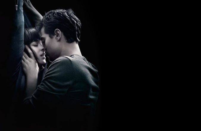 An image from Fifty Shades of Grey showing Ana is pressed against the left of the image with her arms above her head and Christian leaning over her to kiss her