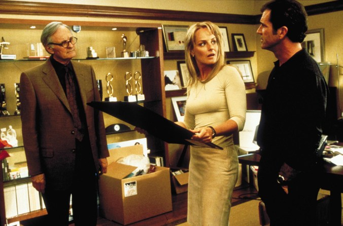 Helen Hunt is holding a poster board and looking over at Mel Gibson