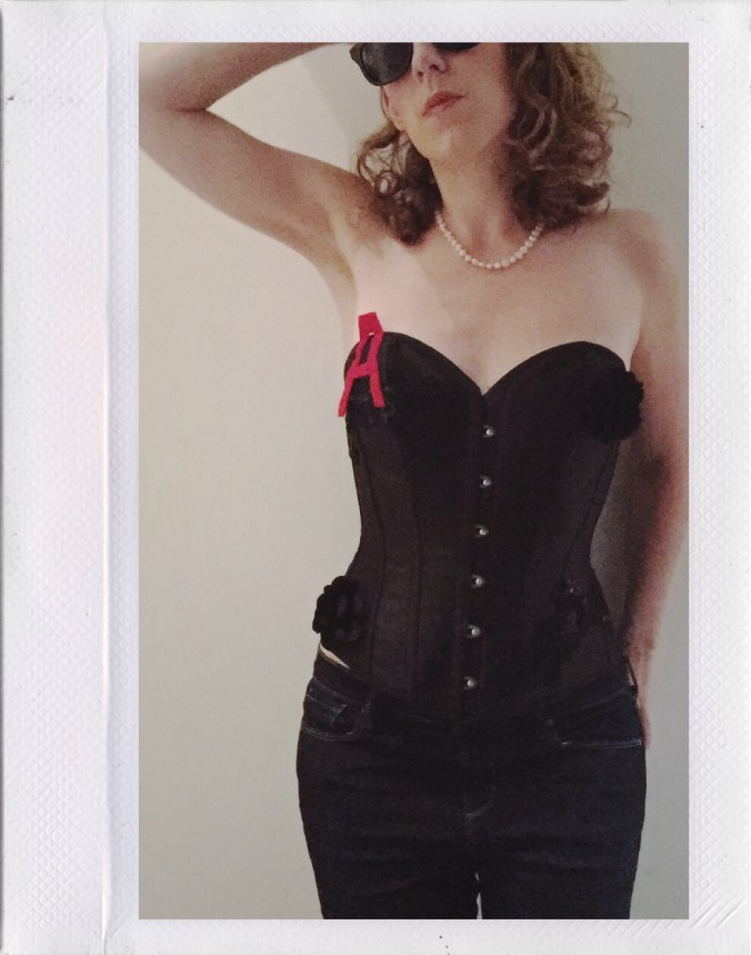 Me, posing in a black corset with red A, sunglasses and pearls