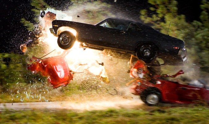 Two cars dramatically colliding, the black flying over a red