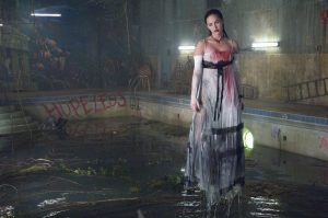 An image from Jennifer's Body showing Jennifer in a prom dress, covered in blood, floating above a dirty pool