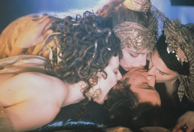 Image from Dracula showing Reeves on the bed with three vampire women kissing him