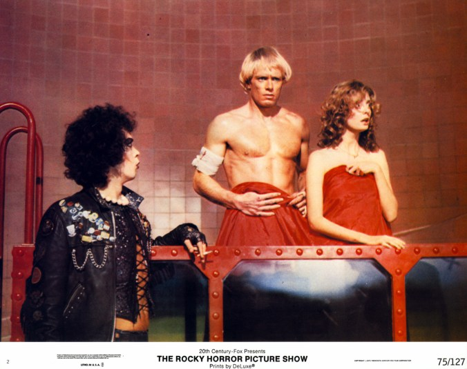 An image from Rocky Horror showing Janet and Rocky wrapped in a blanket