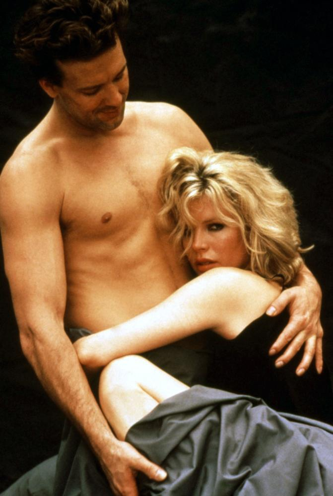 An image from Nine 1/2 Weeks of a shirtless John being embraced by Elizabeth