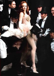 Satine in Moulin Rouge surrounded by men who desire her