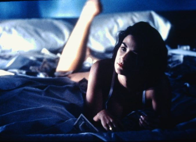 A scene from Indecent Proposal of Demi Moore lying semi-naked on a bed covered in cash