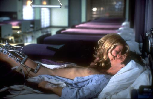 Spader and Unger, kissing, with Sapder in a hospital bed. An image from Crash