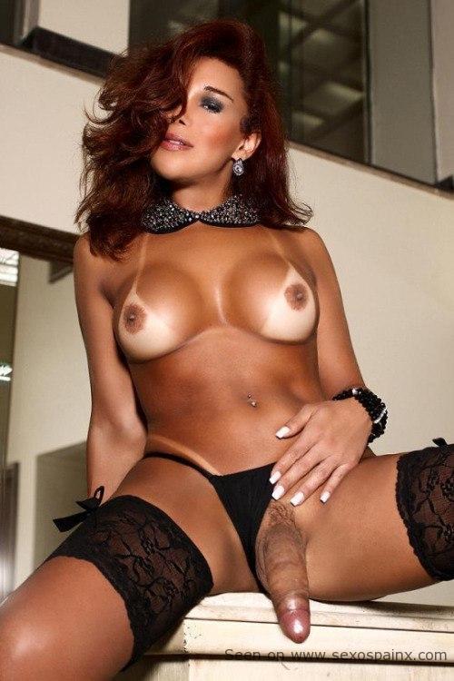 Bronceada mujer transexual en lenceria negra y marcas de tomar el sol