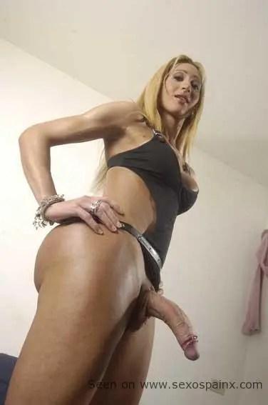 Rubia travesti con el rabo descapullado bien duro y colgando hacia abajo.