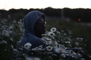 Image: A man with dark skin in a hooded sweatshirt and glasses sitting in a field of daisies