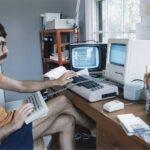 Homem usando computador antigo