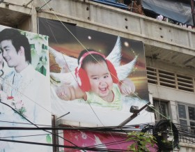 This massive photo of a baby with 4 wings, chubby arms and ear muffs is amazing! Actually almost fall off the moto laughing at it! IN YOUR FACE ANNE GEDDES BABY PHOTOS! KAPOW!
