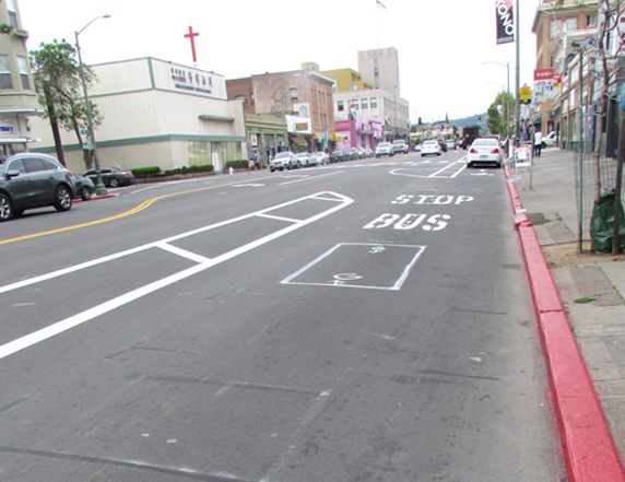 """The bike lane will continue through the bus stops, with a buffer to the left for passing when safe. The box below the word """"bus"""" will be painted green."""