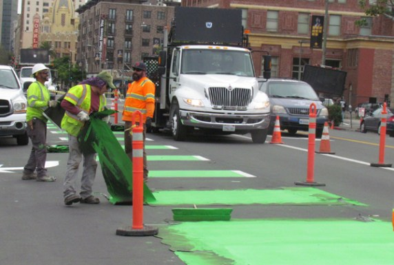 Workers pull up stencils on green lane markings. All photos: Melanie Curry/Streetsblog