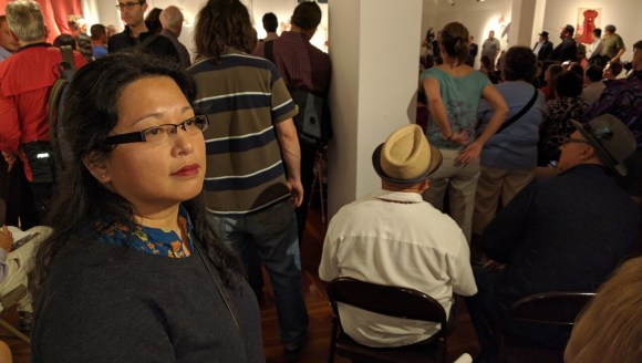 Christina Castro, who spoke in favor of the lanes for the San Francisco Transit Riders, catches her breath at the back of the sweltering room full of angry people Monday night. Photo: Streetsblog.