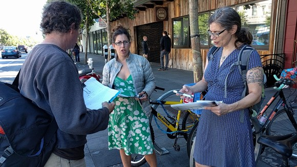 Catherine Orland (green dress) gives instructions on what to look for when counting bike lane violations on Valencia. Photo: Streetsblog.