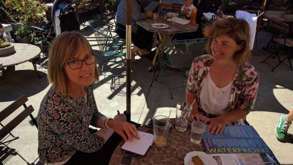 "Cyndy Johnsen (glasses) and Lucy Gigli in the coffee shop ""office"" of BikeWalk Alameda. Photo: Streetsblog."