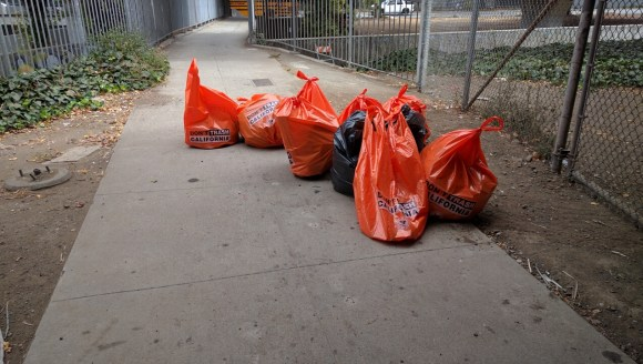 Caltrans workers piled trash bags on the east bound bike path. Photo: Streetsblog.